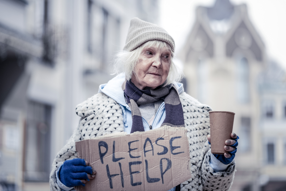 Very poor. Homeless aged woman holding a paper glass while asking people for money