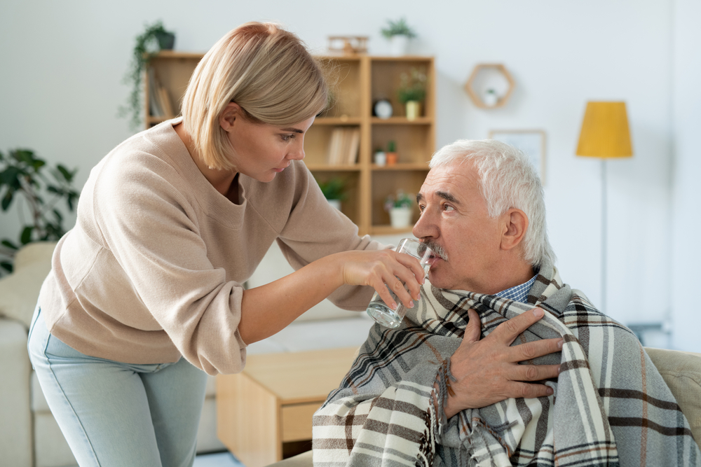 Careful young woman taking care of her sick senior father wrapped in plaid while giving him glass of water