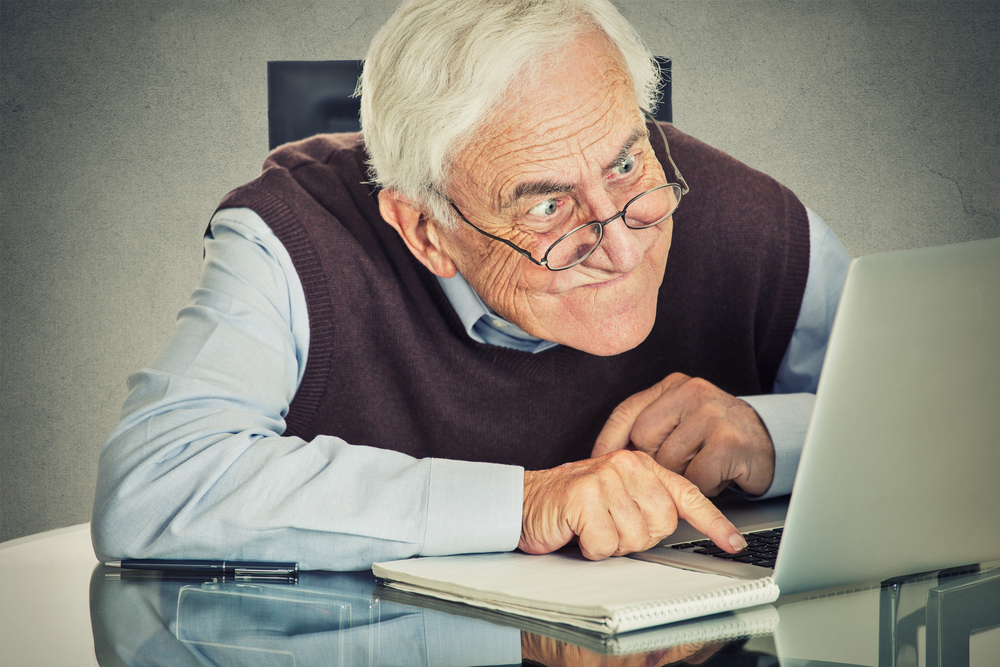 Elderly old man using computer sitting at table isolated on grey wall background. Senior people and technology concept