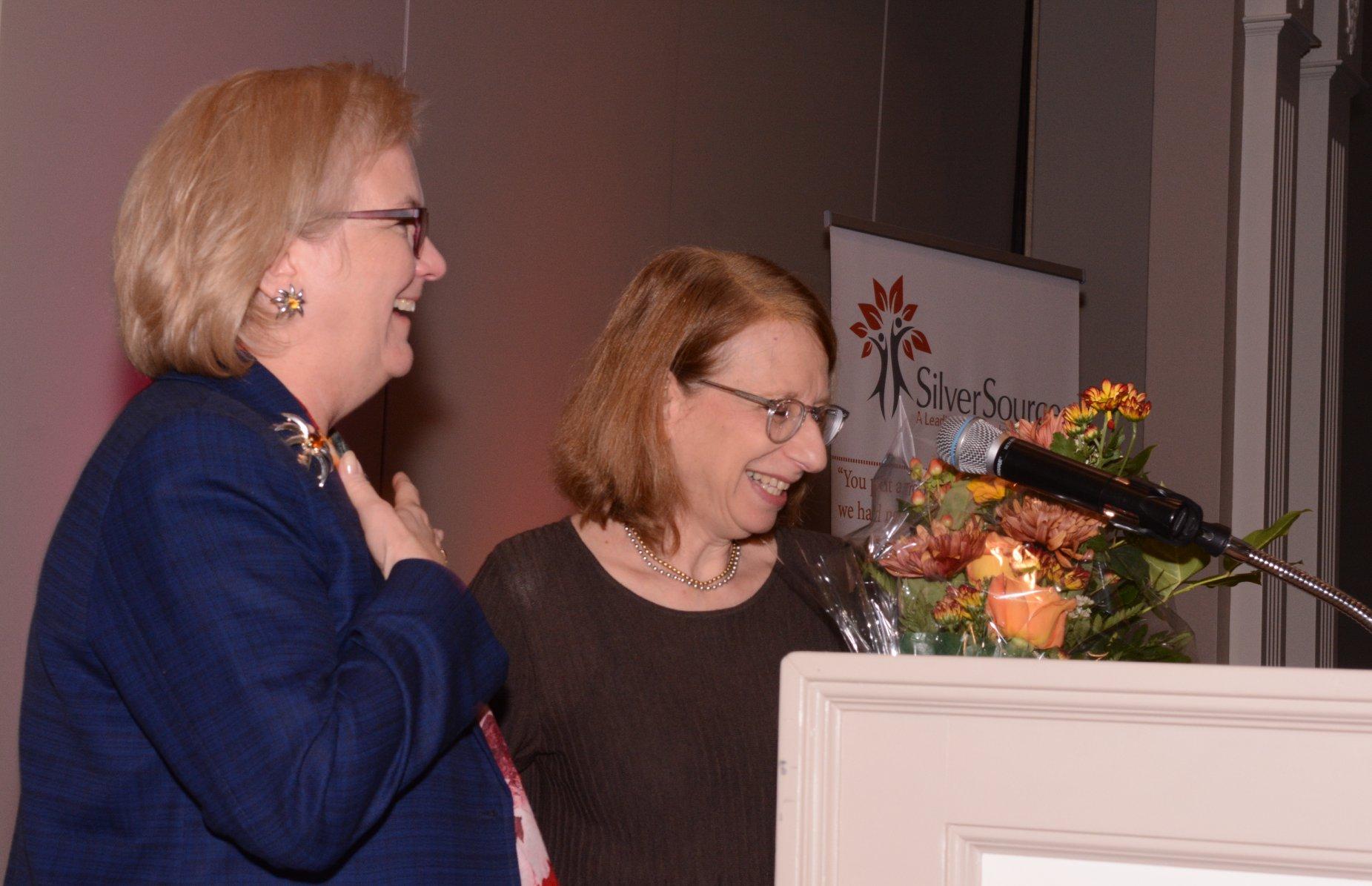 23-Kathleen Bordelon and Roz Chast laughing at podium